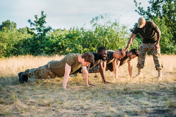tactical instructor examining multicultural soldiers in military uniform doing push ups on range