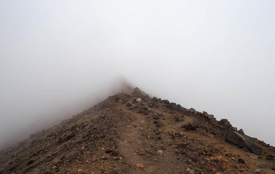 Winding dirt path disappear into fog on Asahidake ridge in Hokkaido, Japan