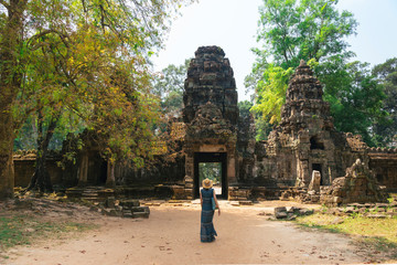 A tourist girl walks among the ancient temple buildings in Angkor; Cambodia.A young woman makes an exciting trip to the temple complex of Angkor.Scenic view of the ruins of ancient temples in Cambodia