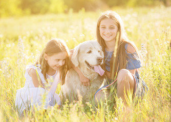 Two young girls cuddling retriever dog outdoors