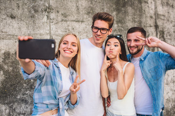 Cool picture of company standing together on grey background. Blonde girl is taking selfie of her company. She is smiling and showing piece symbol. Her friends are also posing but in a funny way.