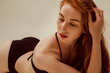 Model shoot in studio. Skinny girl with red long hair posing in the black knitted swimsuit bikini lying on the floor in warm tones