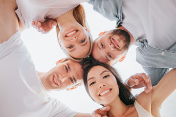 Nice picture of positive teens holding their heads close to each other and looking down on camera. They are smiling. There are two boys and two girls. They are holding each other hands on shoulders.