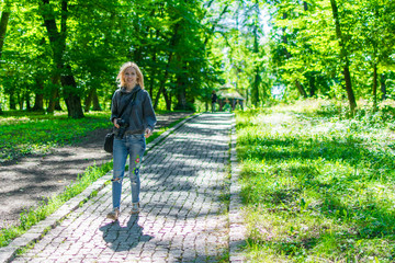 A woman photographer is walking along a forest path with a camera.