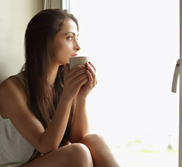 Beautiful lonely woman sitting near the window and looking sad holding the cup of coffee in hand. Closeup portrait