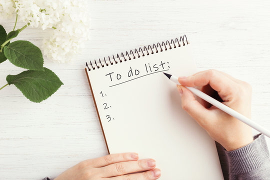 Woman's hand writing To do list in notebook on white wooden table. Working place and planning concept, top view.