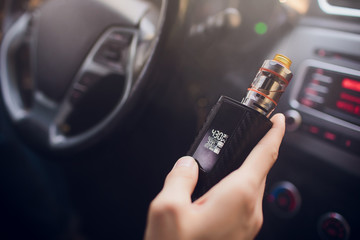 View from the side of a young man smoking an e-cigarette as he drives his car on an urban street Holds and adjusts the power of the electronic cigarette