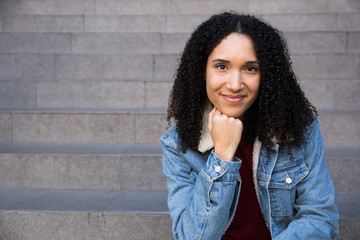Pretty African-American woman in denim jacket sitting on stairway outdoors leaning on hand and smiling at camera