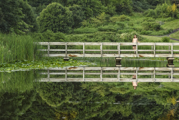Reflections, wooden bridge and girl