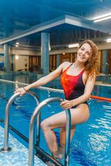 Beautiful sporty girl in swimming pool, aqua fitness concept