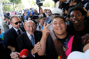 French Interior Minister Gerard Collomb poses for a photo with residents during a visit to the Cite de la Castellane housing complex as part of a trip on day-to-day security in Marseille