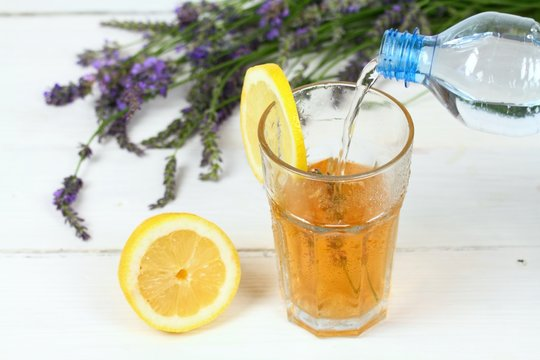 Making homemade lemonade / Pouring soda water into lavender syrup. Made from fresh aromatic lavender flowers, sugar or honey and lemon juice