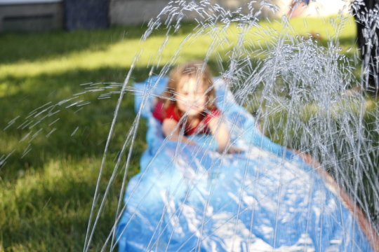 Smiling girl sliding down an outdoor slip and slide. selective focus on water in front of child