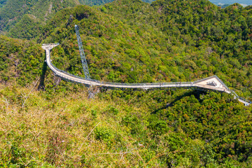 High-angle shot of Langkawi Sky Bridge, a curved bridge with a triangular viewing platform at each end of the walkway, suspended by cables from one pylon at the peak of Gunung Machinchang, Malaysia.