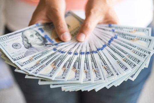 woman hands holding us dollar bills.