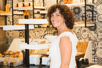 Smiling woman in bakery buy french baguette
