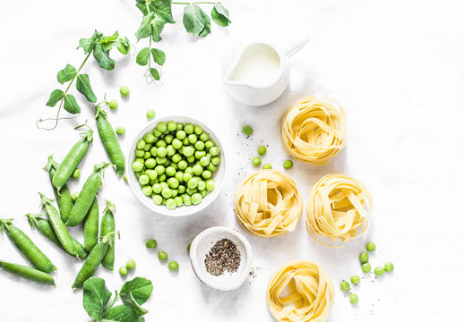 Mediterranean style healthy food ingredients for cooking lunch - fettuccine pasta, fresh green peas, cream, spices on a light background, top view. Flat lay