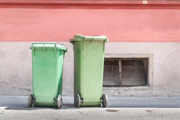 Two green plastic garbage cans on the street with junk and litter waiting for dumpster truck to collect the trash