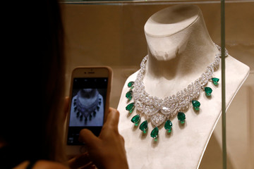 A woman takes picture of high jewellery from the Red Carpet 2018 Collection displayed at the luxury jeweller Chopard store in Paris
