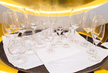 Close up of many empty glasses on tray in restaurant with gold background, free space. Crystal glasses ready for celebration on table. Champagne, wine, cognac glasses at luxury wedding reception