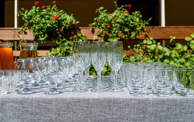 Rows of empty glasses on table outdoors, free space. Set of sparkling glassware, close up. Crystal glasses ready for celebration on table. Wineglasses at luxury wedding reception outside