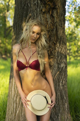 Beautiful blonde sexy slim girl ass wearing only red bra without a panties passionately bending, is leaning her back against the tree trunk and shyly covering her nakedness with her hat.