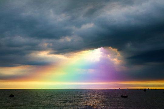 rainbow back dark cloud on sea. concept god bless, wish