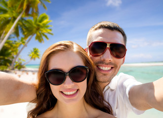 travel, tourism and summer vacation concept - smiling couple wearing sunglasses making selfie over tropical beach background in french polynesia