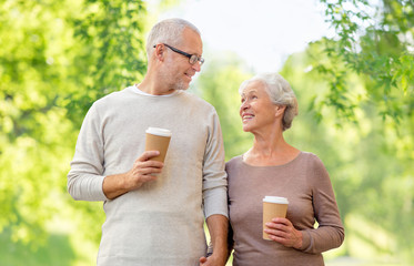 old age and people concept - happy senior couple with coffee cups over green natural background