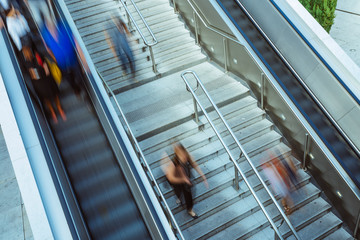 People on stairs and moving escalator at the interchange station near business and commercial center in Paris. Urban scene, city life, public transport hub and traffic concept. Blurred background