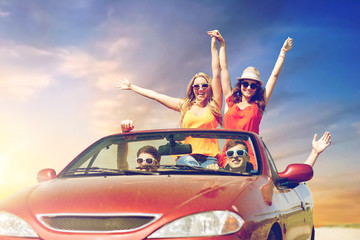 leisure, road trip, travel and people concept - happy friends driving in convertible car at country and waving hands over sky background