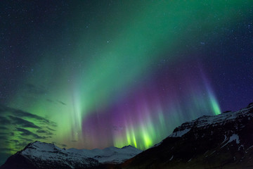 Northern lights above snowy mountains on Iceland