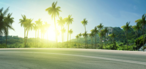 Summer background of road with palms and sunset time