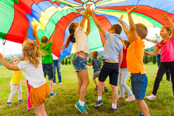 Joyful friends trying to catch flying parachute