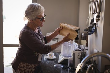 Senior woman putting milk in coffee maker