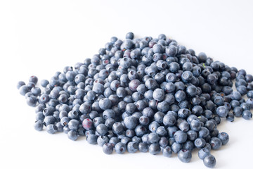 Blueberries on a white background close up, soft focus. Summer wild berry