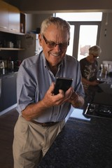 Senior man using mobile phone in kitchen