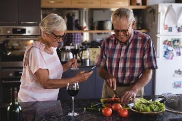 Senior couple cutting vegetables in kitchen