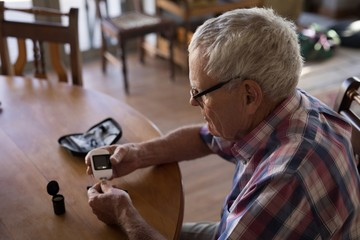 Senior man checking his blood sugar with glucometer