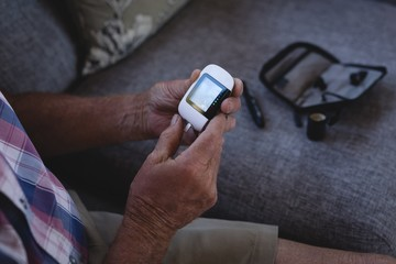Senior man checking his blood sugar with glucometer