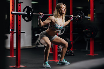 Squats with a barbell in the gym, the development of leg muscles, strengthening of the spine after injuries.