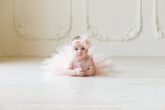 Baby girl wearing a peach tutu. Cute smiling baby girl lying on the floor on creamy background