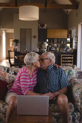 Romantic senior couple kissing each other in living room