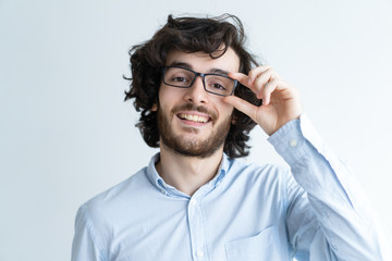 Smiling young dark-haired man adjusting glasses. Attractive guy looking at camera. Smart man concept. Isolated front view on white background.