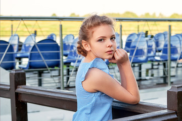 Portrait beautiful caucasian child girl of 9-10 years. Relaxing summer day, outdoors, pier. Kid standing near wooden railing, looks the camera from behind. lifestyle.