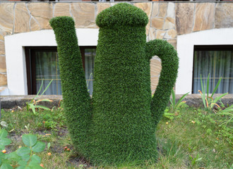 Figure of kettle made of green lawn grass in the park, free space. Green grass covered topiary kettle, landscape design. Grass figure of kettle, topiary figure