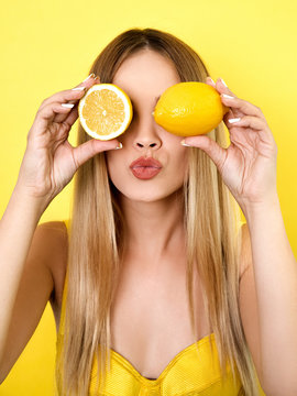 Blond young woman holding lemons