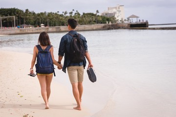 Couple walking together on the beach Wall mural