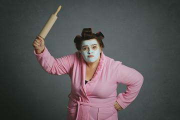 femme ronde et drôle avec bigoudis frappant avec un rouleau à pâtisserie