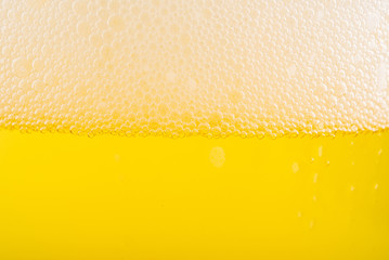 Pouring beer with bubble froth in glass for background.